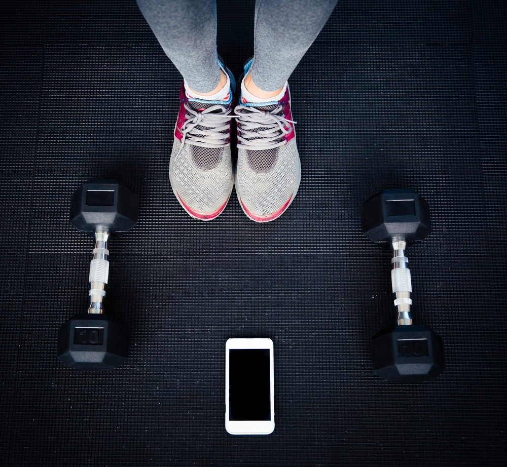 Closeup image of a female legs with dumbbells and smartphone on the floor at gym.jpeg