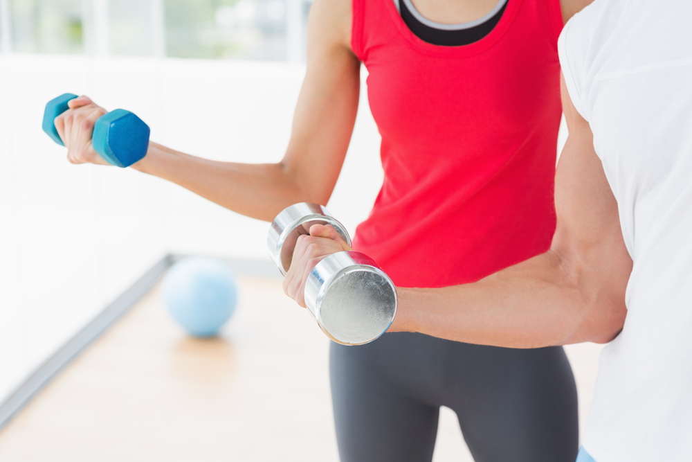 Close-up mid section of a sporty young couple with dumbbells in the gym